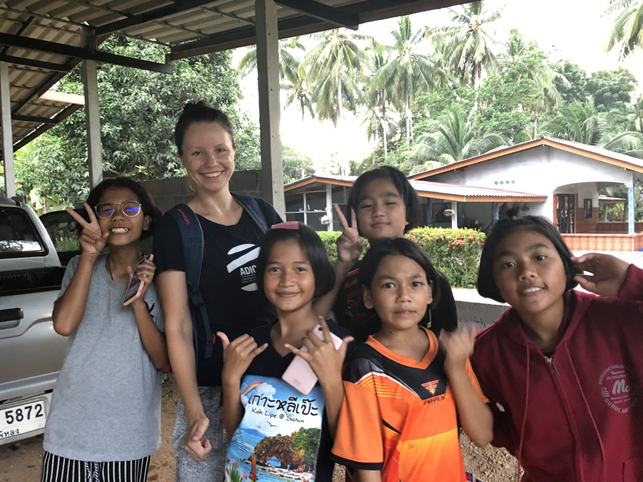 Image of smiling volunteer Akvile in Thailand with local children and beneficiaries