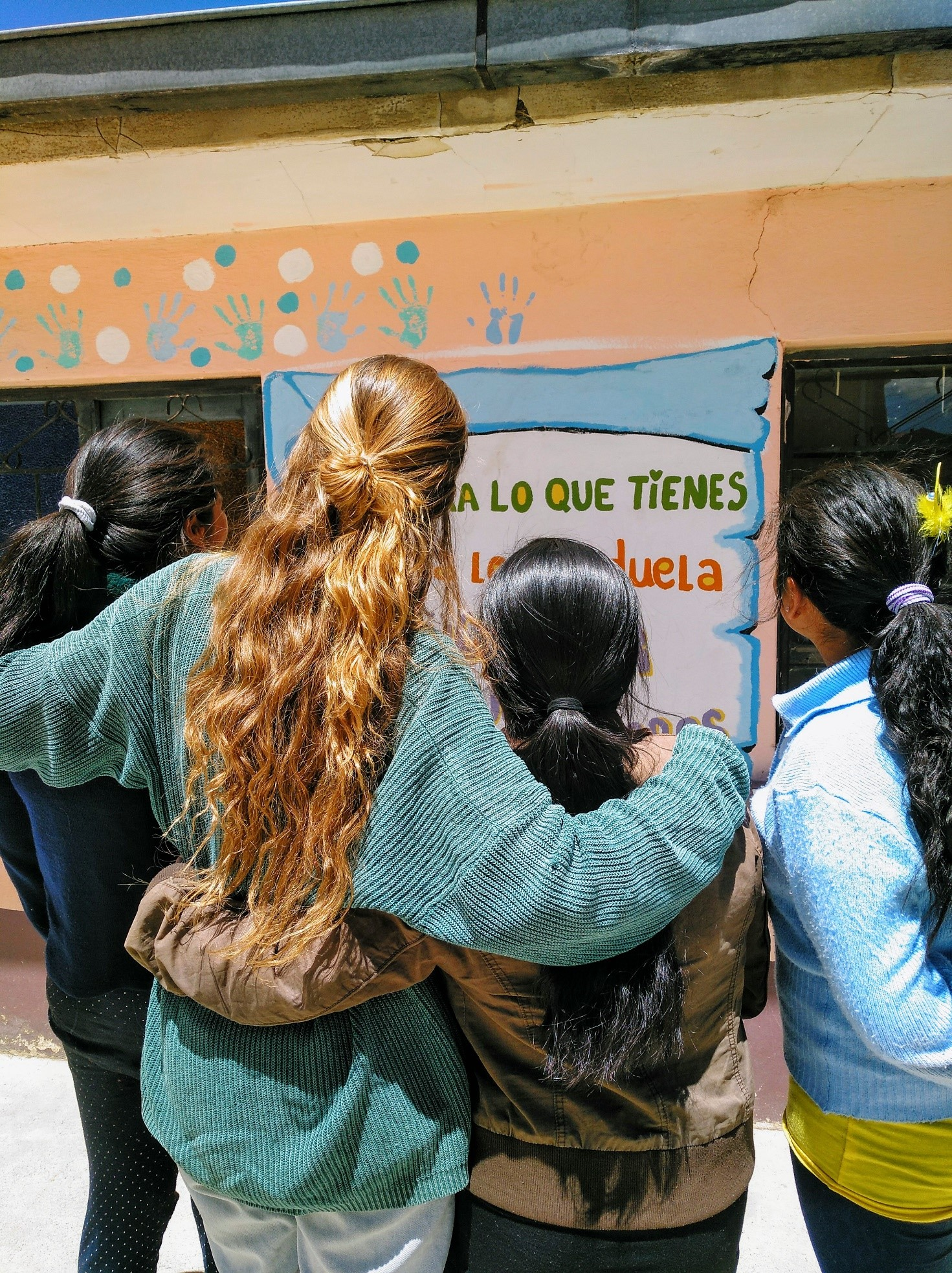 Image of Celia in Bolivia standing with her back to the camera and her arms draped across the shoulders of two women. There is a fourth woman in the photo to the right of Celia.