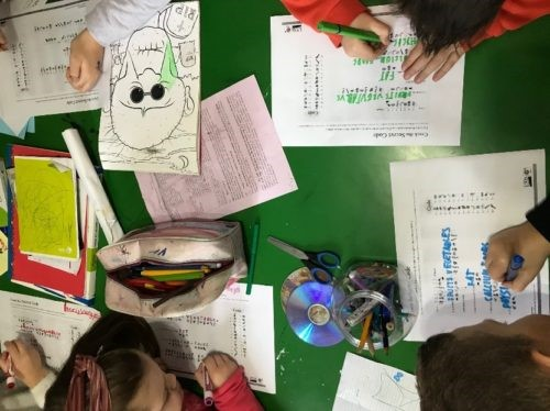 An image of 5 children doing worksheets. The photo is taken from above and none of their faces are visible.