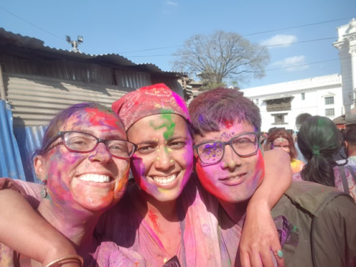 Image of Michaela at HOLI colour festival in Nepal. She has purple, pink and green paint on her face and her arms are drapped around the shouldlers of two friends.