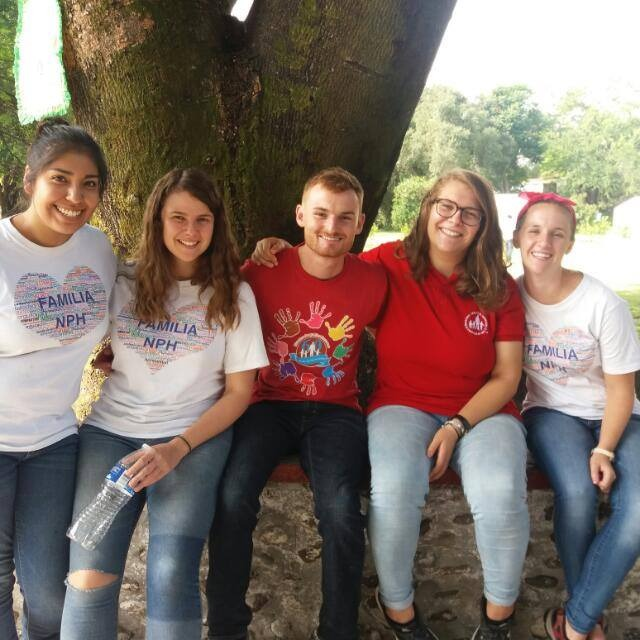 Image of Hazel sat on a low wall next to four of her fellow volunteers, all are smiling and wearing NPH t-shirts.